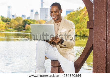 Business Man Working. Dressing in cream blazer, collarless sweater, white pants, wearing a wristwatch, a young black guy is sitting by a lake in a big city, smiling, working on laptop computer.  - stock photo