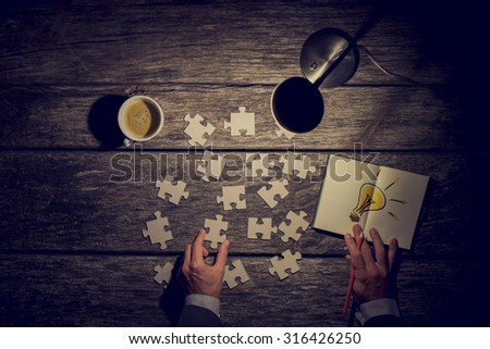 Business man working late at the office trying to find a solution in a concept with an overhead view of his desk and hands by lamp light with puzzle pieces, coffee and a light bulb for bright ideas. - stock photo