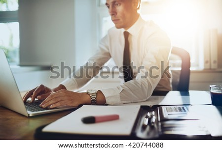 Business man working on a laptop at office with documents on his desk, wearing suit and tie - stock photo