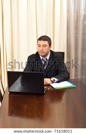 Business man working on laptop in office and being serious