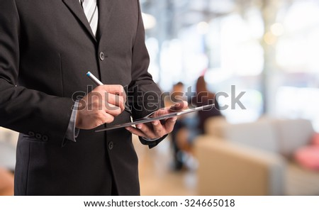 Business man working with a digital tablet on abstract blurred background - stock photo