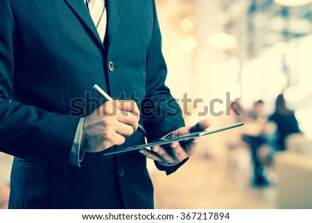 Business man working with a digital tablet on abstract blurred people background, success and profitable business concepts,vintage process style - stock photo