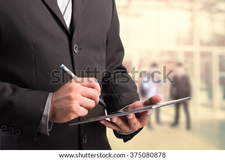 Business man working with a digital tablet on abstract blurred people background, success and profitable business concepts - stock photo