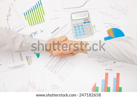Business man working with financial data - shaking hands before signing contract - stock photo
