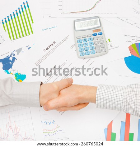 Business man working with financial data - shaking hands over contract - studio shot - stock photo