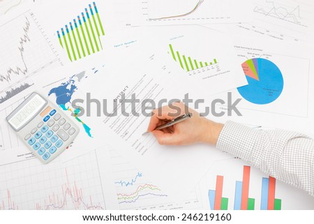 Business man working with financial data - signing contract with pen - stock photo