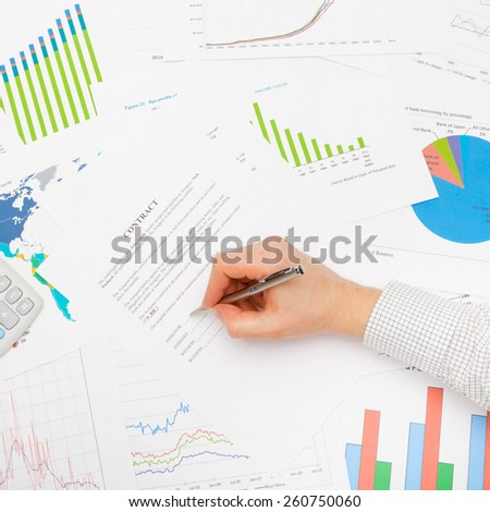 Business man working with financial data - signing contract with pen - studio shot - stock photo