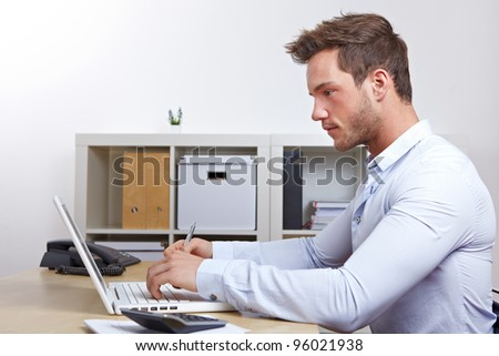 Business man working with laptop computer in office at desk - stock photo