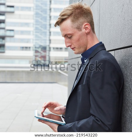 Business man working with tablet computer outside in the city - stock photo