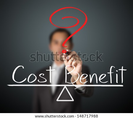 business man writing cost and benefit compare on balance bar - stock photo