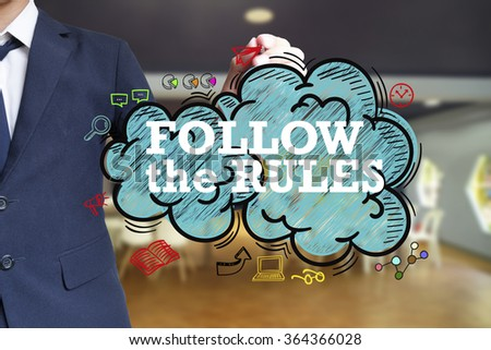 business man writing FOLLOW THE RULES over the cloud with office background , business concept , business idea - stock photo