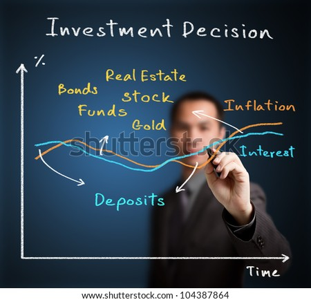 business man writing investment decision according to interest and inflation different - stock photo