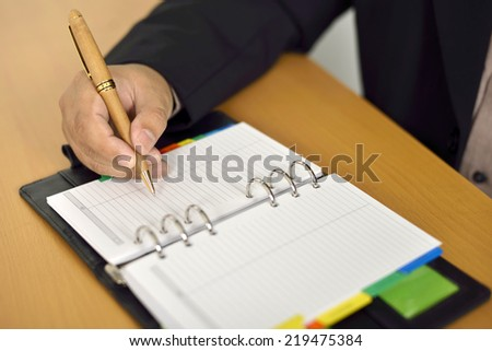 Business man writing on agenda over office desk - stock photo