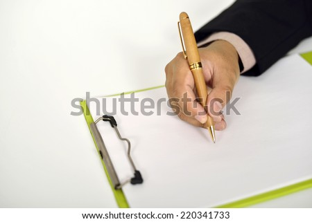 Business man writing on clipboard on the desk