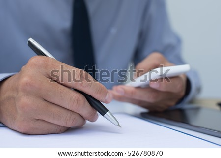 Business man writing on notepad  with ballpoint pen and holding mobile smart phone in office room, close up, online working concept.