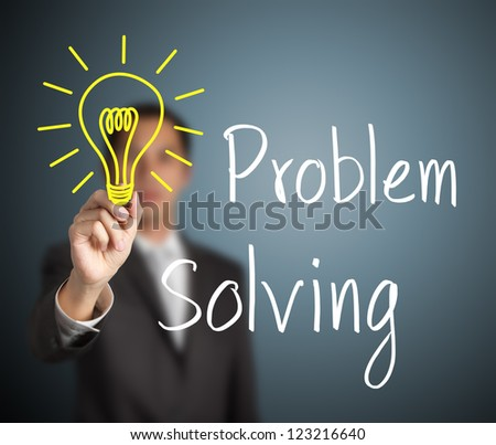 business man writing problem solving light bulb - stock photo