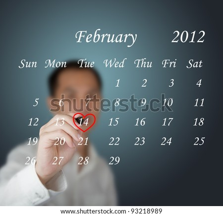business man writing red heart mark at valentine day on calendar