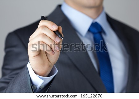 Business man writing something on glass board with marker close-up - stock photo