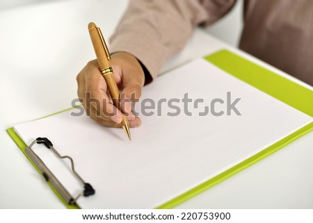Business man writing something on the clipboard