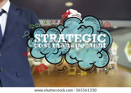 business man writing STRATEGIC COST MANAGEMENT over the cloud with office background , business concept  - stock photo
