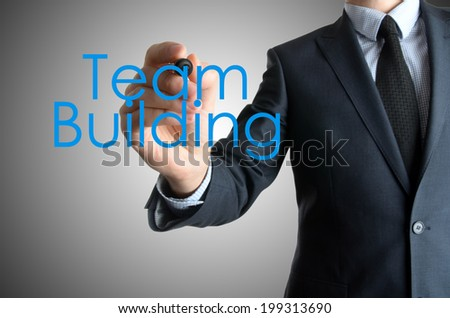 business man writing team building concept on grey background - stock photo