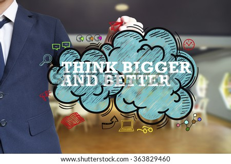 business man writing THINK BIGGER AND BETTER over the cloud with office background , business concept , business idea - stock photo