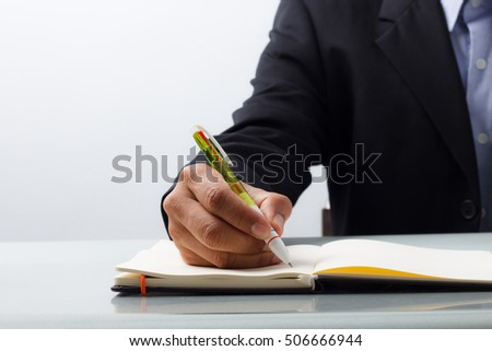 Business man writing with pen at the desk