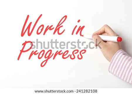 Business man writing work in progress word on whiteboard  - stock photo