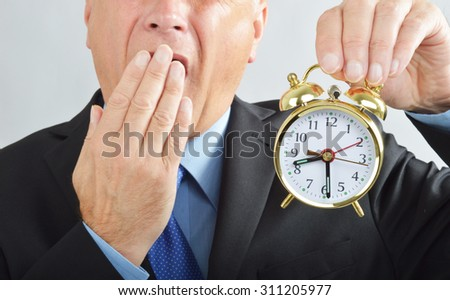 Business man yawning at alarm clock