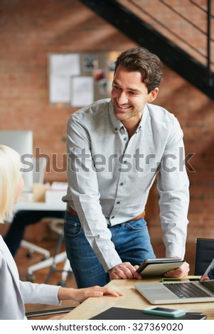 Business manager discussing work with colleague in busy office studio - stock photo