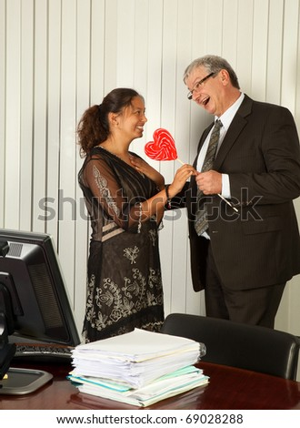 Business manager giving a heart shaped lollipop to his Assistant on Secretary Day