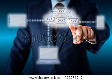 Business manager in blue suit touching a swarm of emails shaping a virtual cloud at the center of a wireless computing network. Laptop, smart phone and tablet computer are linked to the email cloud.