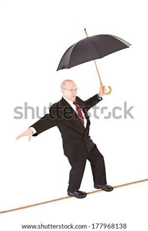 Business: Manager With Umbrella Walking Tightrope - stock photo
