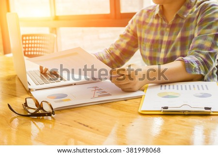 Business mansitting at beautiful wooden desk and using digital computer while typing something on keyboard,freelancer working with laptop in home interior, morning light,selective focus,vintage color - stock photo
