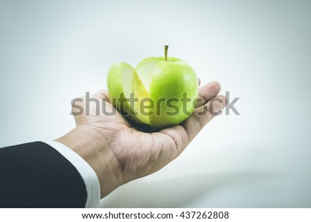 Business market share and success concept.Green apple slice on businessman hand. - stock photo