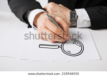 business, marketing, planning and people concept - close up of male hands with pen drawing lens on white paper