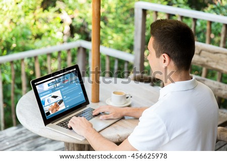 business, mass media, people and technology concept - close up of businessman typing on laptop with news web site on screen outdoors on summer terrace and drinking coffee - stock photo