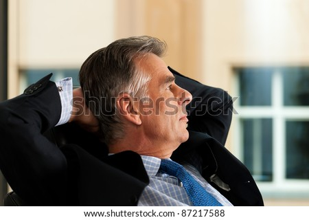 Business - mature boss contemplating in his office; he is looking out of the window - stock photo