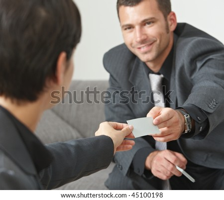 Business meeting at office lobby, people sitting on sofa changing business cards. Focus on card. - stock photo