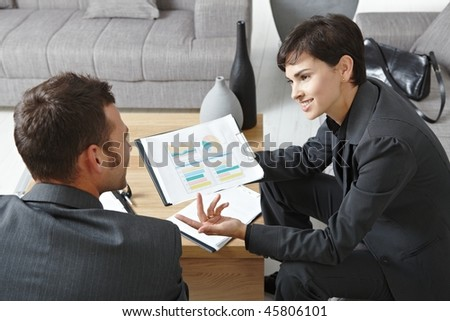 Business meeting at office. Youing businsspeople sitting on sofa, talking over financial charts. Overhead view. - stock photo