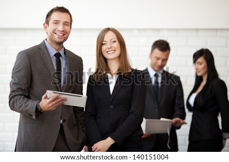 Business meeting. Businesswoman and businessman standing with digital tablet smiling. Selective focus with people in background.