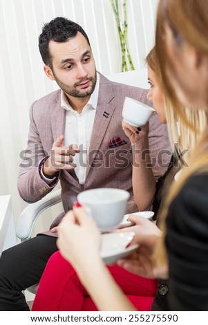 Business meeting, casual conversation with coffee at office, one man two beautiful females. - stock photo