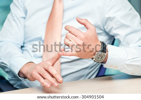Business meeting. Confident businessman sitting at the table at the meeting. Close-up view of the hands of successful businessmen. Businessman showing hand gestures - stock photo