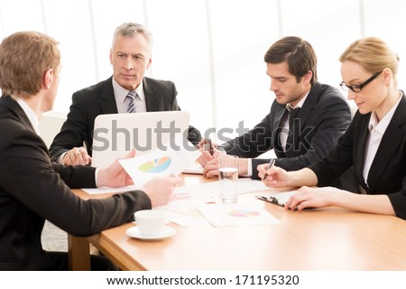Business meeting. Four business people in formalwear discussing something while sitting together at the meeting - stock photo