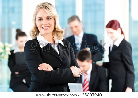 Business - meeting in an office, a colleague is looking into the camera - stock photo