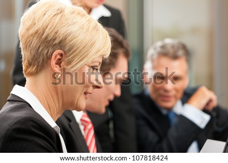 Business - meeting in an office, the businesspeople are discussing a document - stock photo