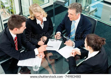 Business - meeting in an office; the businesspeople are discussing a document - stock photo