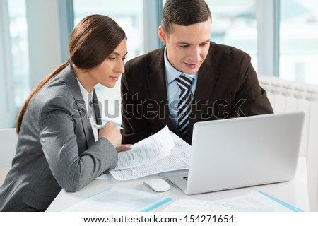 Business meeting in an office - two business people man and woman discussing their plans and reports - stock photo