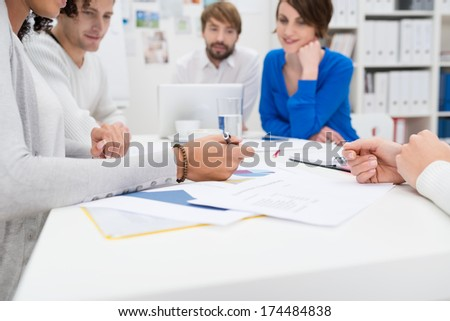 Business meeting in progress in the office with a low angle view down the length of the table of a diverse group of young businesspeople sitting talking - stock photo