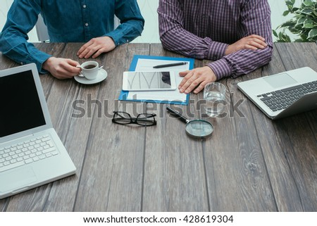 Business meeting in the office: two businessmen are working together at desk, teamwork and partnership concept - stock photo